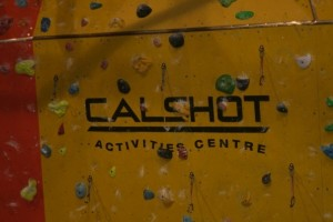"Yellow indoor climbing wall with multiple coloured climbings holds and the centres logo ""Calshot Activity Centre"" written in black across the middle of the wall."