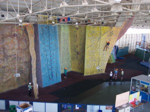 Pan view of Calshot climbing walls.  Shows several of the centres climbing walls, each of which is in a different colour, with multiple coloured climbing holds.  The yellow at the far right of the image has a person climbing half way up to the top.