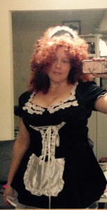 Photograph taken in the mirror of me wearing a French maid outfit, red frizzy permed wig and smiling