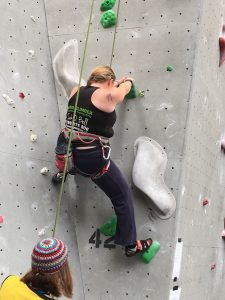 View of me on a grey wall with green holds, using my left foot to balance on the wall beside me