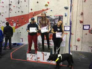 A photograph of the winners in the female VI category, I am stood on the 3rd block, which is not clear as Fizz my guide dog is stood directly in front of me.