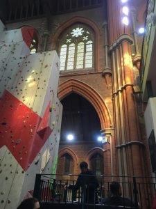 interior image of Manchester Climbing Centre, looking up to a large stain glassed window, above a brick archway, exposed brick and pillars are seen along with a light coloured climbing wall to the left, with different coloured holds and decorative features.