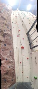 Panaramic photo of a bridging climbing problem with handholds on the central white wall and foot holds on the left stone affect wall and right white wall beside a railing