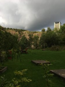 Image of the high quarry walls of Ratho EICA garden, with dark storm clouds behind creating a bright reflection of light from the sun from behind the photographers