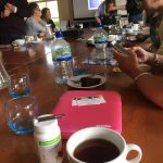 Image of Members of the group sat around a large table with phones, iPads and other tech sat on the table with numerous cups of tea, coffee and water with Molly stood at the head of the table showing her iPad:
