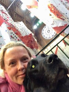 Selfie of me with Guide Dog Fizz with the Climbing Centre behind us and showing a large round stain glass window at the top Centre of the photograph