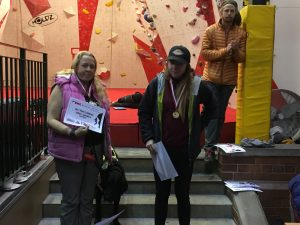 Photograph of me stood on the left hand side of stone steps with a silver medal and certificate with Fizz stood beside me and fellow climber and gold medal winner Abi on the right