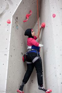 Anoushé is climbing within a 'chimney' at Ratho Climbing centre, she is surrounded by pink jug and bicycles handlebar type holds, her left hand is about head hieght on a hold and she is just moving her right arm, which is covered in white tape at the end onto a similar hold