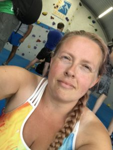 Selfie photograph of me sat inside VauxWall with people climbing behind me and the signage for VauxWall behind me
