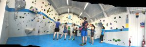 Panoramic photograph of the room hosting the competition in VauxWall with people stood around and some climbing