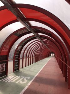 Second photograph shows the arch of the red girders forming over the top of the passageway looking down on the ramp with the green and red path for cycles and pedestrians.