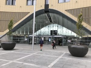 Photograph of the front exterior glass of Dundee relailway station, with it's large archway and inside/outside marching paving.