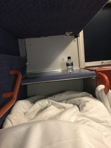 Photograph is taken from where I sat in the bottom bunk in the berth, showing the width of the bed, with a counter at the end of the bed and the sink with a bottle of water on the side