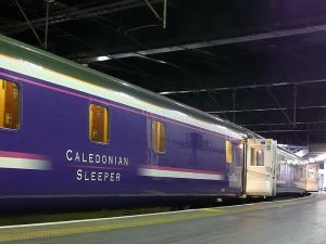 Photograph is of the side of The Caladonian Sleeper train carriage from the platform