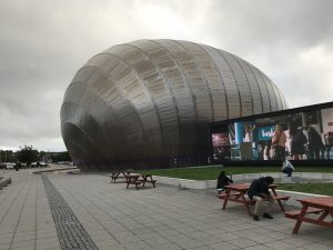 Photograph shows a round ball like building on the left which is Glasgow IMAX with a large screen on the right of the photograph, with a small green area in front of it