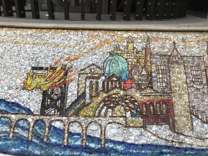 Photograph of Mosaic at Glasgow Queen Street railway station, showing the river cliyde and bridge on the left and the buildings of Glasgow on the left.