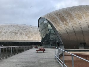 Photograph is taken of the rear of the IMAX building where Starbucks sits amongst a glass wall sat beside part of an old dock area
