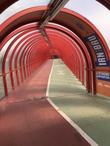 Photograph of red steel girders of a covered over path and cycle path, showing the red and green paths with an arch over the top which is totally enclosed