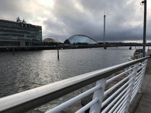 Photograph is taken beside the river Clyde railing, showing across the river with BBC Scotland on the left, with The Glasgow science centre dome shaped building along with The Glasgow tower on the right of the image, The imax cinema can be partly seen in between the bbc building and the science centre