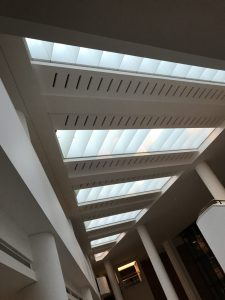 Photograph shows the stripped skylights that run parallel to each other in a triangular flat roof of The British Library