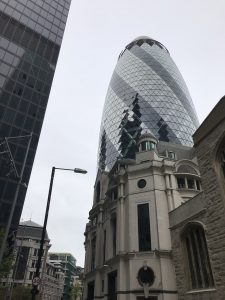 Photograph of The Gherkin building behind a church with the side of The Cheesegraer on the very left of the photo