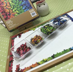 Image of a white board with all the edges of the colourful jigsaw pieces on it.  Sat in the centre is a tray with the separated colours in.