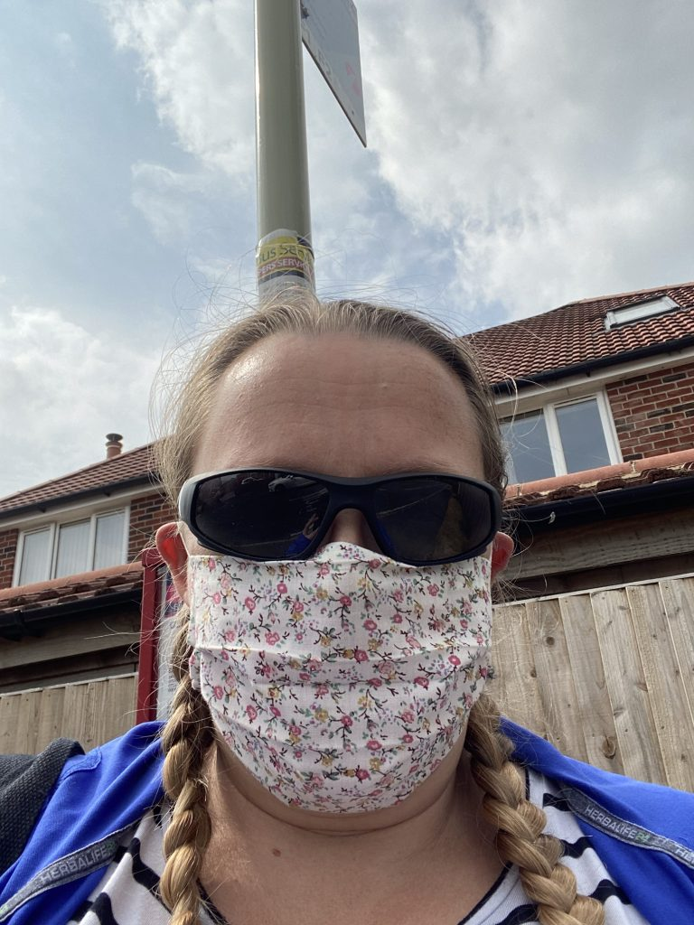 Selfie photo of me wearing a floral face mask and dark sunglasses with the pole for the bus stop behind me