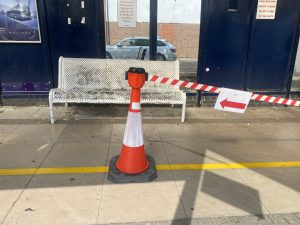 Photo of the inside of Fareham Bus Station, a large metal timetable board is on the left and infront is a orange cone with red and white tape and a sign pointing left to state that this is the direction to walk.  In the background past the tape is a metal bench.