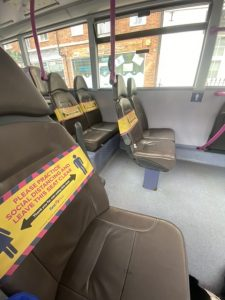 Side on view of grey seats on a bus with many have yellow tape explaining about social distancing on the aisle seats and on both seats every other row