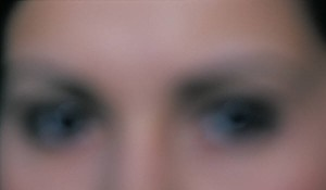 A blurred image of a woman's eyes and the bridge of her nose.