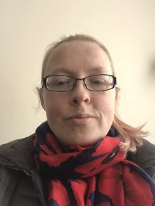 Selfie photograph of my face, with a scarve on that is blue with red popppies. I am wearing my glasses and my hearing aids with my hair