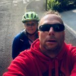 Photograph shows a 'selfie' of Simon smiling at the camera, with me, Tee sat behind him on the left. The photo is of us both sat on the Tandem, but the bike is not in the shot.
