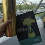 Photograph of my gold Starbucks travel mug with the guide book to The Glasgow Science Centre with the SEC Armadillo building behind across the river Clyde.