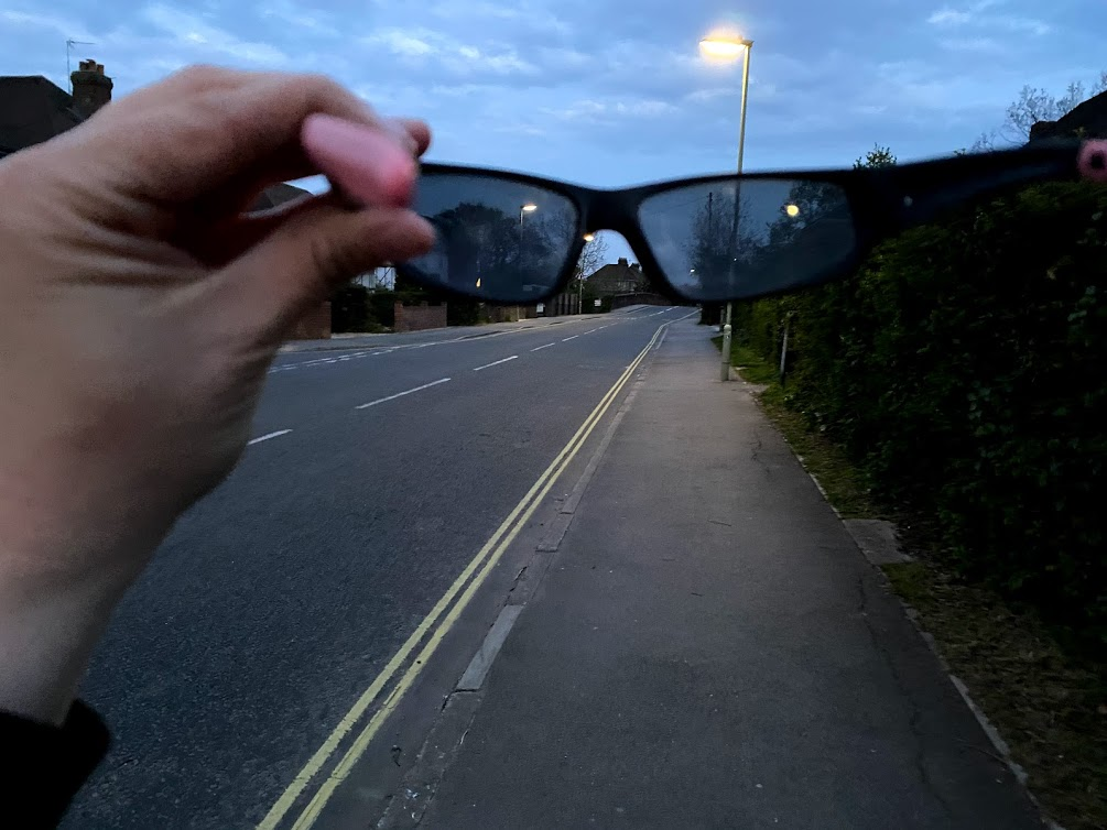 Photograph taken looking through sunglasses, to show the lighter sky and street light outside the sunglasses, with a darker tint and glare reduction though the sunglasses